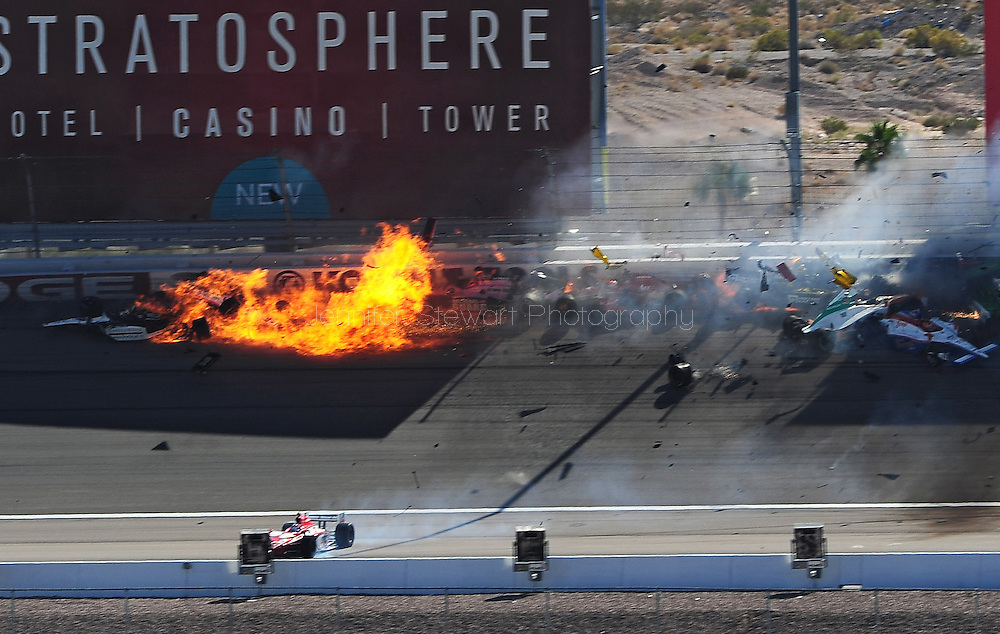 The car of Indy Car series driver Dan Wheldon (far left) catches fire after crashing into the wall as Will Power (12), J.R. Hildebrand (4), Wade Cunningham (17), and Charlie Kimball (83) collide during the IZOD IndyCar World Championships at Las Vegas Motor Speedway. Indy Car series driver Dan Wheldon died from injuries suffered in the 15-car crash. Mandatory Credit: Jennifer Stewart-US PRESSWIRE