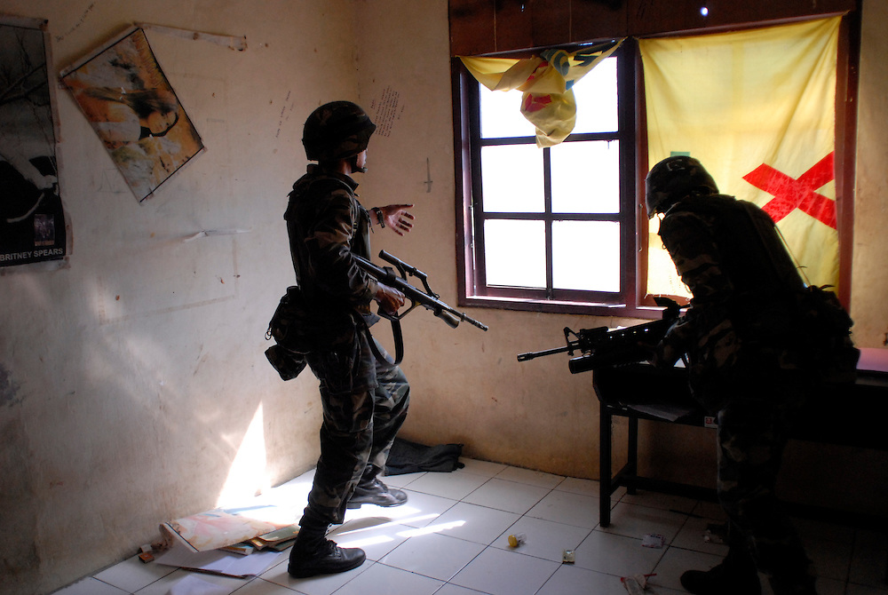 Malaysian troops search house to house, after rumours of a gunman brought them to the Comora area of Dili. Later, gangs loot and burn nearby buildings. 04/06/06