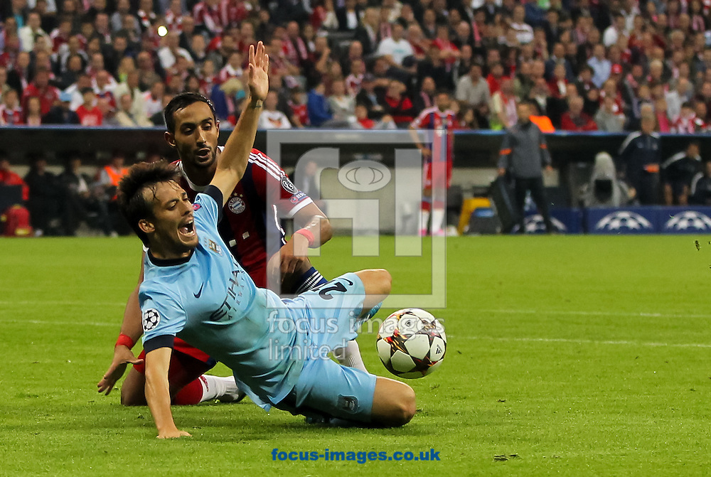David Silva (front) of Manchester City is tackled in the penalty area by Mehdi Benatia (back) of Bayern Munich during the UEFA Champions League match at Allianz Arena, Munich<br /> Picture by Tom Smith/Focus Images Ltd 07545141164<br /> 17/09/2014