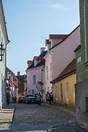 Tallinn, Estonia -- July 23, 2019. Pedestrians walk along a side street in Tallin, Estonia.