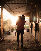 Woman in equestrian attire carries her young daughter near the horse stable at sunset.<br />