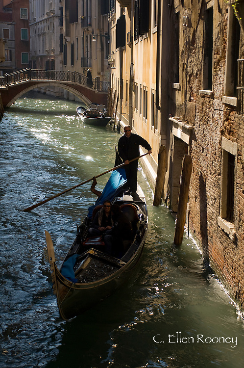 Tourists taking a gondola ride along a small canal;  Venice, Italy