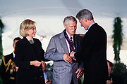 Musician Doc Watson is presented the National Medal of Arts by President Bill Clinton and First Lady Hillary Clinton during a ceremony on the South Lawn of the White House September 29, 1997 in Washington, DC.