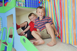 Two boys sitting at the top of slide in mobile playbus,