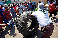 A group of protestors rolls a truck tire in front of the mayors office Tuesday Sept. 11, 2007, Palin Guatemala. A angry mob took to the streets and went on to burn down the mayors office as well as his home in demonstration after and clash with local police on the previous day. Residents accuse the mayor of, among other things, of bussing voters for the elections on Sept. 9 2007.   (photo by/ Darren Hauck)............