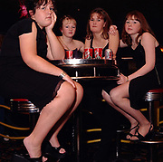 A group of teenage girls, sat on stools, looking bored, Cardiff, UK 2000's