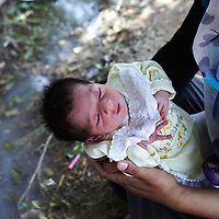 Syrian refugee 10 day old Hawler is held by her mother Peroz Ismail, 27-years-old, next to a pool of water infected with mosquitos next to their blanket in Quashtapa Park in Quashtapa, Iraq outside of Erbil in Iraqi Kurdistan, Friday, August 30, 2013. For the past week the family has been living on a blanket with hundreds of other Syrian refugees in a small park on the outskirts of Erbil. August 2013.