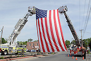 Middletown, NYcc  -  A large American flag hangs between two fire department ladder trucks on the route of a Memorial Day parade  on May 25, 2009.