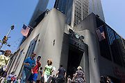 American consumers pass the tall doorway of the East River Savings Bank in Lower Manhattan, New York City.