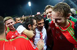 ZENICA, BOSNIA & HERZEGOVINA - Saturday, October 10, 2015: Wales' Gareth Bale, goalkeeper Wayne Hennessey and Chris Gunter celebrate with manager Chris Coleman qualifying for the Euro 2016 finals despite a 2-0 defeat to Bosnia and Herzegovina during the UEFA Euro 2016 qualifying match at Stadion Bilino Polje. (Pic by David Rawcliffe/Propaganda)