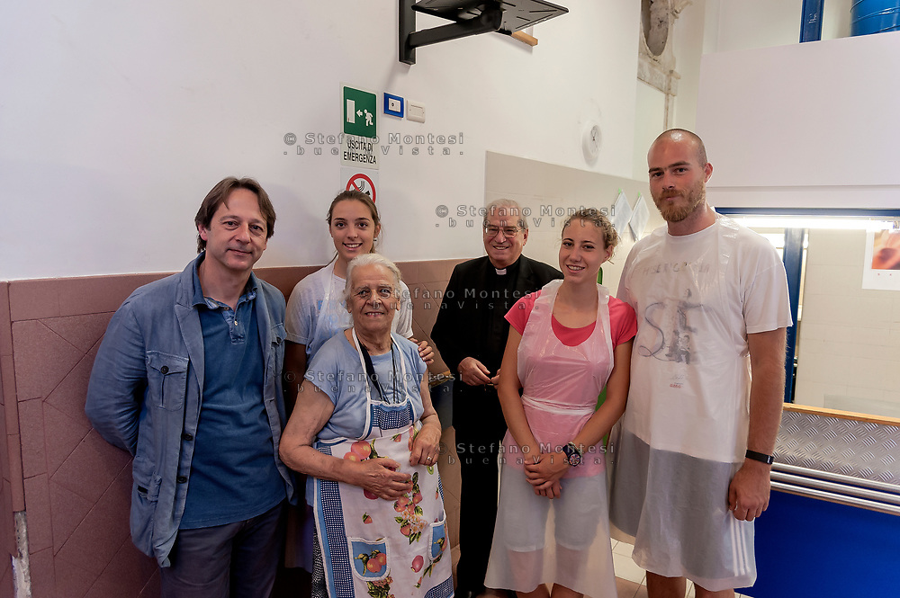 ROME, ITALY - AUGUST 15: The director of Caritas Rome, Msgr. Enrico Feroci and the Deputy Mayor Luca Bergamo with a volunteers during visits the Caritas canteen of Colle Oppio on the mid-August holiday on August 15, 2017 in Rome, Italy. Caritas canteen of Colle Oppio  provide about 500 meals a day for lunch.