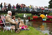 Dagjesmensen kijken naar het varende Bloemencorso van het Westland. Boten gedecoreerd met bloemen, groente en fruit varen voorbij.