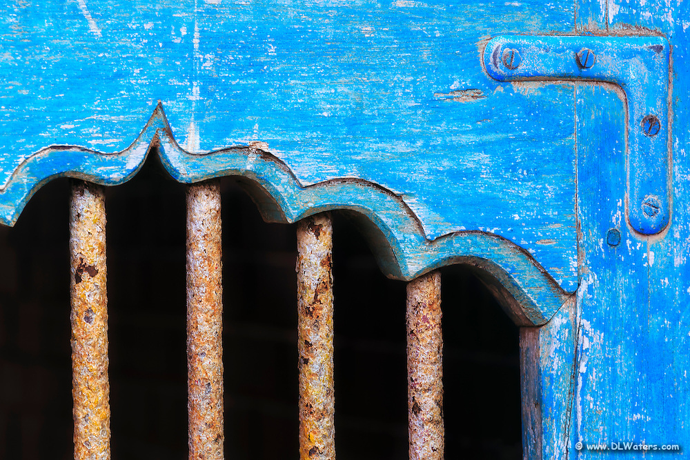 Detailed shot of a blue gate with bars.