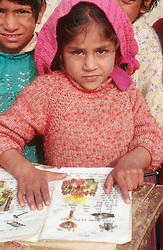 Young boy reading book at primary school in Patiala; Punjab,
