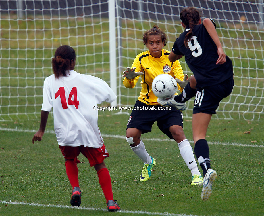 NZ's Martine Puketapu shoots but is stopped by New Caledonia's Deborah Selefen. OFC U-17 Women's Championship, New Caledonia v New Zealand, Centre Park Mangere, Wednesday 11th April 2012. Photo: Shane Wenzlick