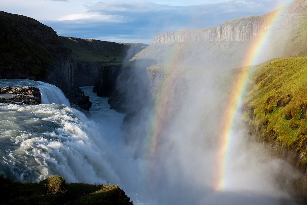 Iceland, Rainbow forms as Hvita River pours over Gullfoss waterfall at dawn on summer morning