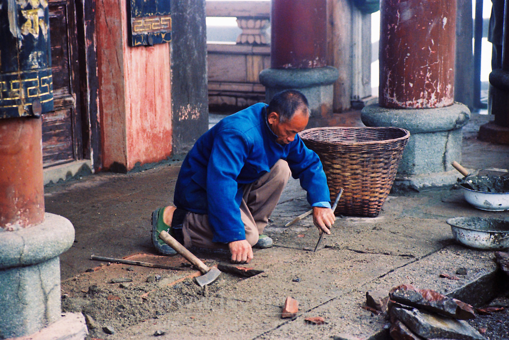 China, Emei Shan, 2007. Mountain-top temple maintenance is hard work for this stonemason, working in the cold and mist that envelops Emei Mountain in summer..
