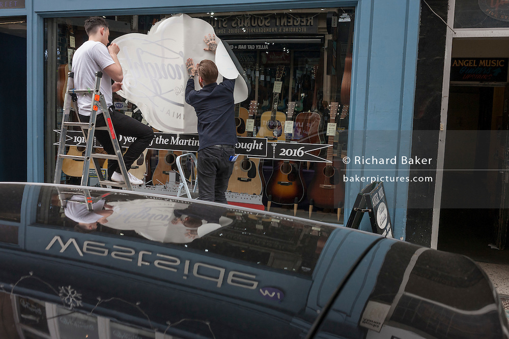 Two employees of musical instrument retailer Westside apply a transfer for the Martin Company's Dreadnought guitar brand in Denmark Street, Tin Pan Alley, Soho, London.