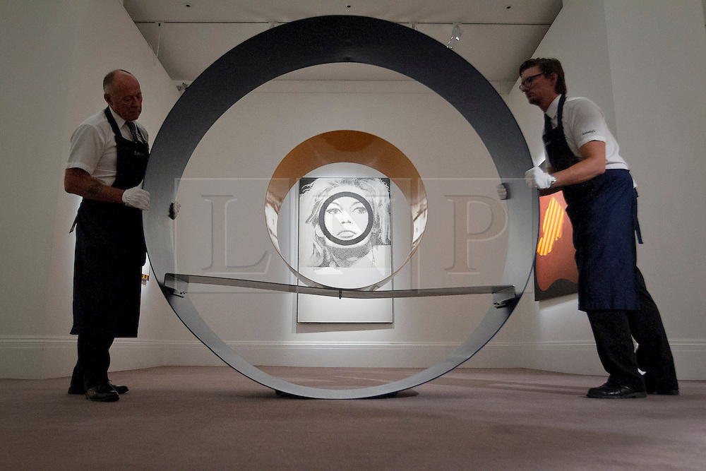 "© Licensed to London News Pictures. 03/09/2013. London, UK. Two Sotheby's employees adjust David Annesley's ""Untitled (Circle)"" (1966) with Gerald Laing's ""Bridget Bardot"" (1963) in the background during the press view for an exhibition of art from the 1960's at Sotheby's in London today (03/09/2013). The exhibition, entitled ""The New Situation: Art in London in the Sixties"" and located at the auction house's New Bond Street building, is open to the public from 4th to the 11th of September 2013. Photo credit: Matt Cetti-Roberts/LNP"