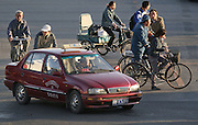 "Beijing, China - October 13, 2005 - Chinese cyclists share the road with a ""Charade"" taxi or Xiali in Beijing October 13, 2005. Buyers of small-engine, low-emission cars are set to get tax breaks as the government tries to reduce oil consumption and pollution."