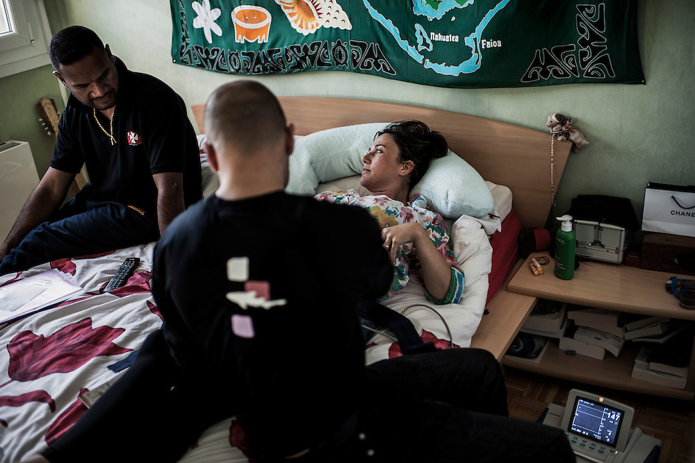 Soan, 16th BC French unit soldier, is pictured at home with his wife, 6 months pregnant, and the male midwife listening to the heartbeat of their future child, on October 20, 2012 near Lyon. AFP PHOTO / JEFF PACHOUD
