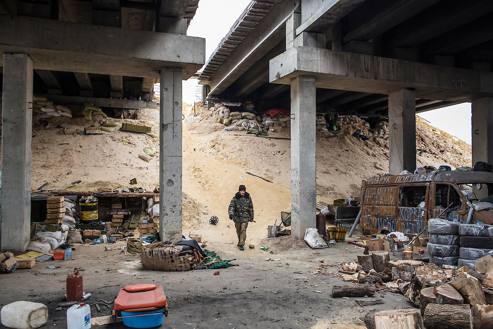 "PERVOMAISKE, UKRAINE - NOVEMBER 17, 2014: ""Patrick,"" a member of the 5th platoon of the Dnipro-1 brigade, a pro-Ukraine militia, at their post underneath a bridge in Pervomaiske, Ukraine. CREDIT: Brendan Hoffman for The New York Times"