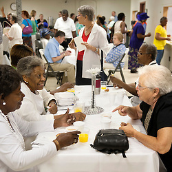 2 AUG. 2015 -- ST. LOUIS -- Parishioners and visitors gather for coffee and donuts following Mass Mob III at Sts. Teresa and Bridget Catholic Parish in St. Louis Sunday, Aug. 2, 2015. The event brings Catholics from across the Archdiocese of St. Louis to worship at historic, urban parishes.<br /> <br /> Photo by Sid Hastings.
