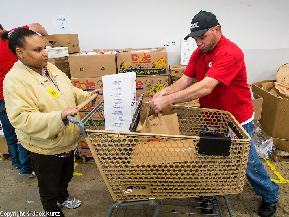 05 NOVEMBER 2013 - PHOENIX, AZ: A volunteer at St. Mary's Food Bank in Phoenix, AZ, packs carts for clients. Demand at St. Mary's has continued to increase even as government assistance is reduced. Over the summer, St. Mary's Phoenix location provided emergency food for 300 - 400 families per day. They are currently supporting about 600 families per day. Part of the increase is seasonal but a large part of it is no clients coming to the food bank for the first time. More than 1.1 million Arizonans who use the Supplemental Nutrition Assistance Program, known as food stamps, saw their benefits reduced Friday, Nov. 1, in a long-planned national cut that was tied to the economic stimulus which was a part of the American Recovery and Reinvestment Act. The cuts imposed last week range from $11 a month for a single recipient to $65 or more for large families. Many of SNAP receipients already use food banks to supplement their government assistance and the cuts in the SNAP program are expected to increase demand even more.   PHOTO BY JACK KURTZ