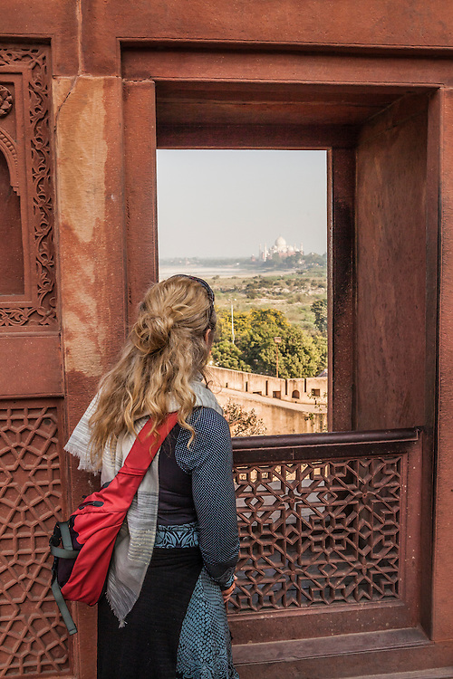A woman in Agra Fort looking out a window toward the Taj Mahal, Agra, India.