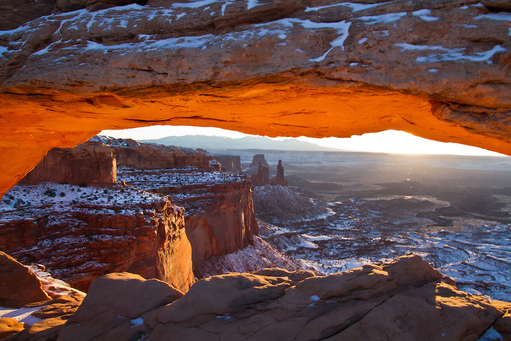 A beautiful Winter sunrise at Mesa Arch in Canyonlands National Park after a fresh blanket of snow covered the desert floor.