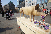 Vienna, Austria. Marie Cochon is a pig feeding on (and stuffed out with) fake money named honey, protesting against greed and corruption in contemporary politics. During her performance, she's assistet by artists Nikolaus and Barbara Eberstaller..http://www.marie-cochon.com