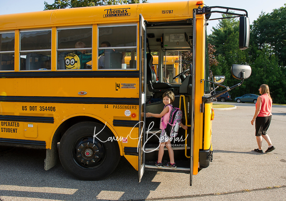 Jasmine Kapplain hops onto the school bus at Woodland Heights that will bring her to Pleasant Street School to begin her first day of Kindergarten on Monday morning.  (Karen Bobotas/for the Laconia Daily Sun)
