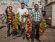 Three men selling offerings to worshippers at Dwarka's temple.