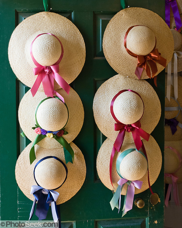Straw hats with red, maroon, pink, green and blue ribbons hang on the door to the Milliner & Tailor shop on Duke of Gloucester Street at Colonial Williamsburg. Colonial Williamsburg is the historic district of the independent city of Williamsburg, Virginia, which was colonial Virginia's capital from 1699 to 1780, and a center of education and culture.