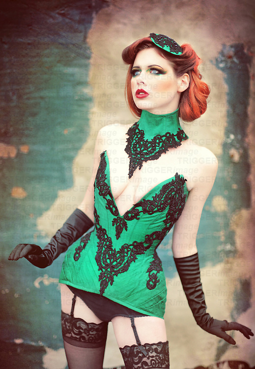 Colorful photo of a beautiful young woman wearing an elaborate green corset, hair piece, underwear, garter and stockings while gazing off into the distance