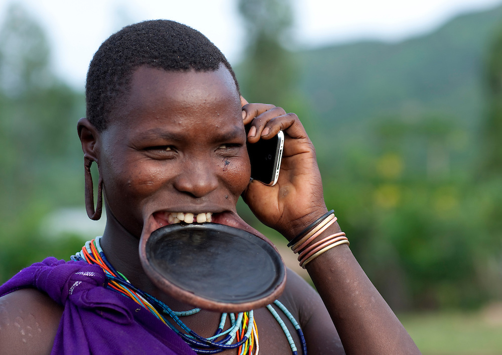 Suri woman with lip plate and mobile phone, Turgit village, Omo valley, Ethiopia.<br /> <br /> Piercing and lip plates are a strong part of the Suri culture. These traditional adornments are worn by almost all the adult Suri women. Ear labrets are worn both by women and men. When a Suri woman is about to be married, usually in her teens (around 14 or 15), she disappears from the village life to live in her family's hut. The gap between her front lip and the flesh below is pierced and gradually stretched. In the beginning a hole is made in the lip with a wooden stick. The stretch continues as successively bigger discs of clay or wood are accommodated by the disfigured lip. Generally the two lower front teeth are pulled (or knocked) out to aid the process. The final size of the plates determines how many cattle the woman will receive as a dowry. Some women have stretched their lips so as to allow plates up to sixteen inches in diameter. Having a lip plate is considered a sign of beauty. The origins of this tradition are unknown. Sometimes the lip is broken by the pressure of the lip plate. This is a very big problem for girls because men will consider them as ugly, and they won't be able to marry anyone in the tribe apart from old men or ill people. Although it is seen as a sign of beauty nowadays, it is said that the disfigurement began as a way to prevent slavers from seizing Surma women. Over the last few years, a growing number of young Suri women refuse to have their lip pierced. The increasing exposure and opening of the Suri to other cultures is the main reason of this trend. Indeed, some Suri teenagers have the opportunity to study in Addis Abeba, and once back in their village, they tend to try to change customs and traditions. Mursis have the same tradition, as Mursi women also wear lip plates ; whereas Nyangatom, including men, wear smaller lip plates.