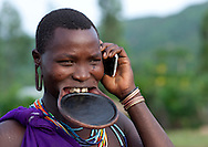 Suri woman with lip plate and mobile phone, Turgit village, Omo valley, Ethiopia.<br />