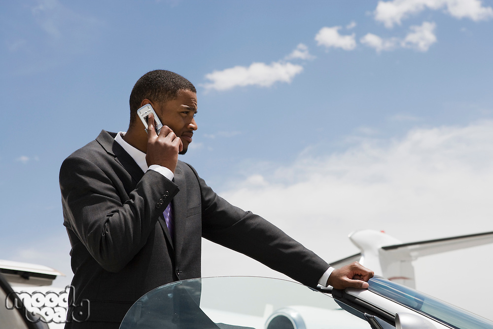 Mid-adult businessman standing in convertible and using mobile phone.