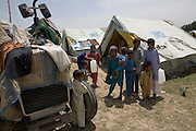 An extended family seek shelter from the scorching sun in a UNHCR tent at Shaik Shazad IDP Camp...Residents from SWAT valley begin arriving at Shaik Shazad IDP camp at outside of Mardan in North West Frontier Province...Within four days more than 2000 families have reportedly registered as IDP's seeking shelter and food at the hastily arranged camp. According to UNHCR Some 500,000 residents have fled SWAT and neighboring provinces since August 2008. On Thursday the Pakistan Government announced a military operation to 'eliminate' Taliban militants form the SWAT Valley. A further 1 million IDP's are expected in the coming weeks as the military advances throughout SWAT valley towards achieving their military goals..
