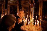 Russian Orthodox worshipper  lighting candles in church in Zagorsk, near Moscow, Russia