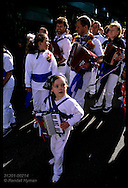 Youngest accordionist marches with elders in morning kids parade before adult festivities on May Day in Padstow; Cornwall, England.