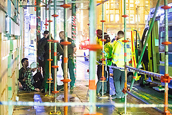 """© Licensed to London News Pictures . 23/12/2017. Manchester, UK. Police and paramedics tend to a man with a head injury , inside a police cordon on Deansgate . Revellers out in Manchester City Centre overnight during """" Mad Friday """" , named for being one of the busiest nights of the year for the emergency services in the UK . Photo credit: Joel Goodman/LNP"""