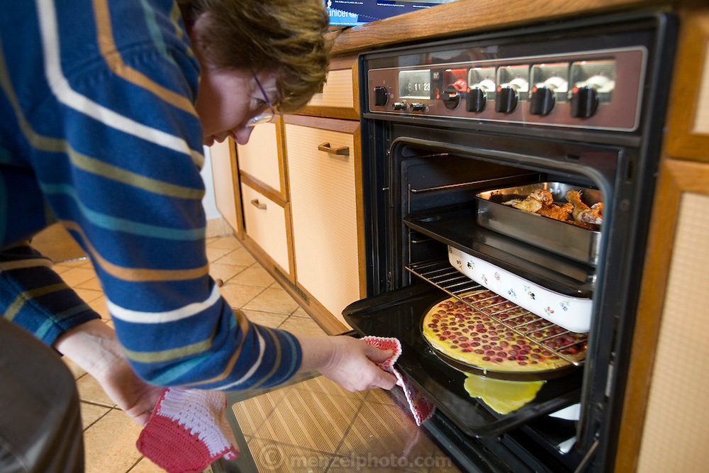 Marie Paule Kutten-Kass of the town of Erpeldange in Bous, southeast of Luxembourg City, near the German border attends to food in the oven. The image is part of a collection of images and documentation for Hungry Planet 2, a continuation of work done after publication of the.book project Hungry Planet: What the World Eats.