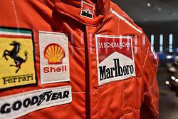 "© Licensed to London News Pictures. 14/11/2017. London, UK.  Racing suit worn by Michael Schumacher to win the 1996 Italian Grand Prix.  Preview of ""Ferrari: Under the Skin"", an exhibition at the Design Museum to mark the 70th anniversary of Ferrari.  Over GBP140m worth of Ferraris are on display from private collections including Michael Schumacher's 2000 F1 winning car.  The exhibition runs 15 November to 15 April 2018.  Photo credit: Stephen Chung/LNP"