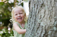 Portrait of young girl (1-2) peeking from behind tree laughing