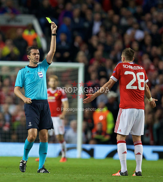 MANCHESTER, ENGLAND - Wednesday, September 30, 2015: Manchester United's Morgan Schneiderlin is shown a yellow card by referee Viktor Kassai during the UEFA Champions League Group B match against VfL Wolfsburg at Old Trafford. (Pic by David Rawcliffe/Propaganda)