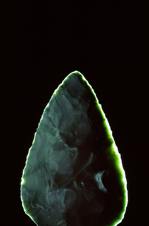 Flint stone spear axe head. Back lit showing sharp knapped translucent cutting edge. Kilmartin House Museum, Scotland