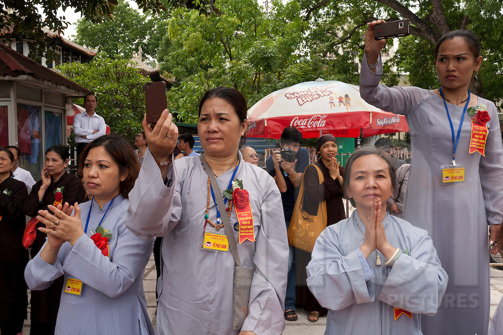Buddhist vietnamese women are praying while others are taking photos during Buddha's birth celebration, Hanoi 2011. Vietnam, Asia