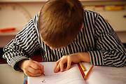 Ein Bub lernt Schreiben in der Schule. Un garçon qui apprends à écrire à l'école, boy writing at school. © Romano P. Riedo