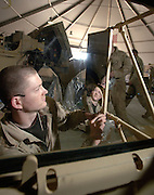 Balad Air Base, Iraq (AFPN) ? Seen through bullet proof glass, Staff Sgt. John See, puts the final touches on a rear view mirror of an armored cab, that sits on the floor of one of the Add on Armor installation shops. Later, this upper cab portion will be raised and lowered onto the lower armor plated cab section already on the truck tractor, similar to the one in the background.  The tractor is receiving a permanent add-on-armor kit.  The armor provides the driver and gunner protection against weapons fire and IED explosions. Sgt. See is deployed to the 732 Expeditionary Logistics Squadron, Balad Air Base, Iraq. The unit is comprised of active duty and reserve component vehicle maintenance technicians who support the Army Field Support Battalion- Iraq. The installation of the Level II Add on Armor (AOA) kits provides a high degree of protection to the troops operating outside the wire. Survivors of improvised explosive device explosions, often e-mail the unit to give their thanks for them doing such a great armor installation job. This, the final phase of the AF mission, will end with the turnover to contractors in late January 2006.  To date the Air Force AoA mission has fielded more than 1,300. See is assigned to the 4th Logistics Readiness Squadron, Seymore Johnson Air Force Base and is a native of Parkersburgh, W. Va. (U.S. Air Force Photo by Master Sgt. Lance Cheung)<br />